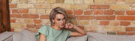 Foto de Imagen horizontal de una mujer guapa y soñadora sentada en un sofá cerca de la pared de ladrillo y mirando hacia otro lado. - Imagen libre de derechos