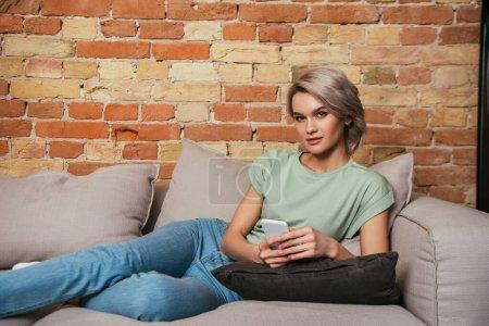 attraktive, selbstbewusste Frau, die auf dem Sofa sitzt, mit dem Smartphone plaudert und in die Kamera schaut