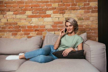 hermosa, mujer sonriente mirando a la cámara mientras se relaja en el sofá y hablando en el teléfono inteligente