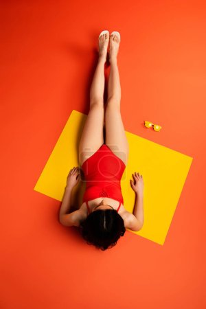 Photo for Top view of girl lying near yellow sunglasses on orange - Royalty Free Image