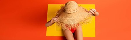 Photo for Panoramic shot of young woman in swimsuit touching straw hat on orange - Royalty Free Image