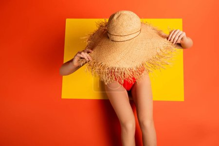 Photo for Top view of young woman in swimsuit touching straw hat on orange - Royalty Free Image