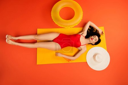 Photo for Top view of girl in bathing suit lying near bottle with sunscreen, inflatable ring, straw hat and mirror on orange - Royalty Free Image