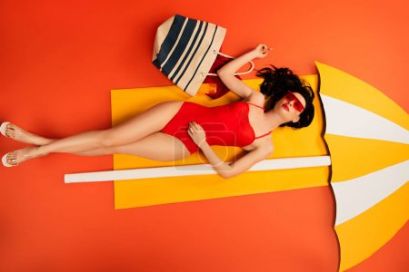 Photo for Top view of beautiful girl in sunglasses and swimsuit lying with bag near paper umbrella on orange - Royalty Free Image
