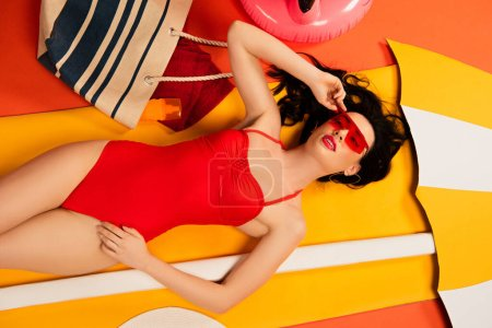 Photo for Top view of beautiful woman in sunglasses and swimsuit touching cap and lying on orange - Royalty Free Image