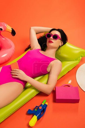 Photo for Stylish girl in sunglasses and swimsuit lying on inflatable mattress near inflatable ring, paper bag with sunscreen and water gun on orange - Royalty Free Image