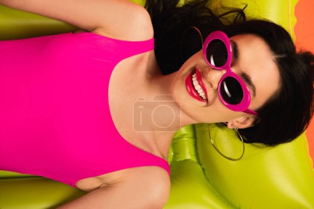 Photo for Top view of cheerful girl in pink sunglasses and swimsuit lying on green inflatable mattress - Royalty Free Image