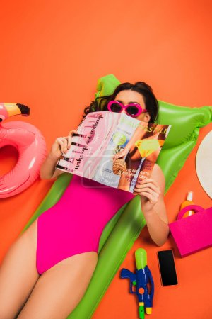 Photo for Young woman in sunglasses and swimsuit lying on inflatable mattress and covering face with magazine on orange - Royalty Free Image