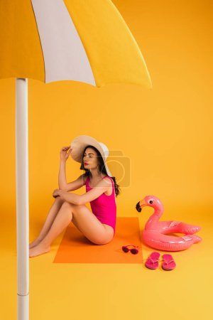 Photo for Attractive woman in straw hat and swimsuit sitting near sunglasses, flip flops, inflatable ring and paper umbrella on yellow - Royalty Free Image