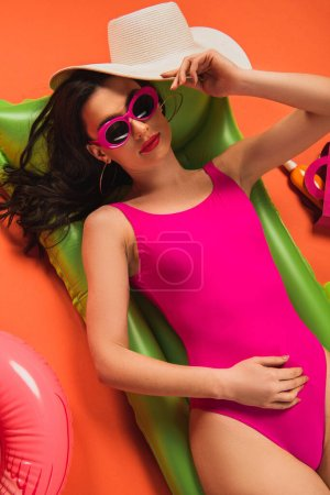 Photo for Top view of beautiful woman in sunglasses and swimsuit lying on inflatable mattress and holding straw hat on orange - Royalty Free Image