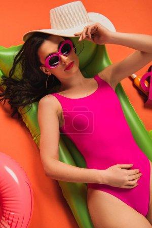 Photo pour Vue du dessus de la belle femme en lunettes de soleil et maillot de bain couché sur un matelas gonflable et tenant un chapeau de paille sur orange - image libre de droit