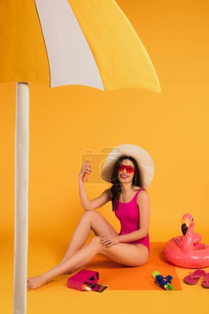 Photo for Cheerful woman in straw hat, sunglasses and bathing suit holding bottle with sunscreen near inflatable ring and water gun on yellow - Royalty Free Image
