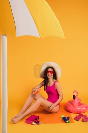 Photo for Cheerful woman in straw hat, sunglasses and bathing suit applying sunscreen near inflatable ring and water gun on yellow - Royalty Free Image