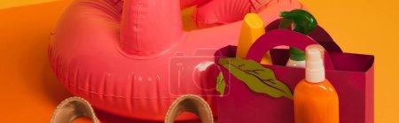 Foto de Concepto panorámico de bolsa de papel con protector solar en botellas cerca del anillo rosado inflable en amarillo. - Imagen libre de derechos