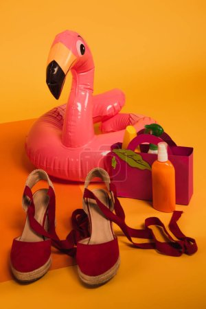 Photo for Paper bag with sunscreen in bottles near pink inflatable ring and platform shoes on yellow - Royalty Free Image
