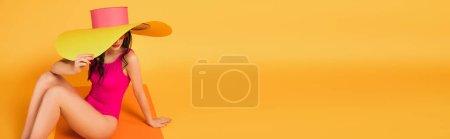 panoramiczna orientacja stylowej kobiety w słomkowym kapeluszu i kostiumie kąpielowym zakrywającym twarz podczas siedzenia na żółtym