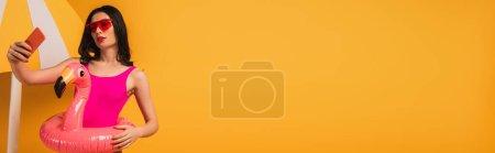 Photo pour Image horizontale de la fille attrayante en lunettes de soleil et maillot de bain debout avec anneau gonflable et prendre selfie sur jaune - image libre de droit