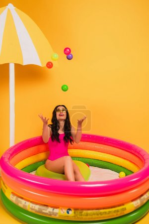 Photo pour Happy girl throwing in air balls while sitting in inflatable pool on yellow - image libre de droit
