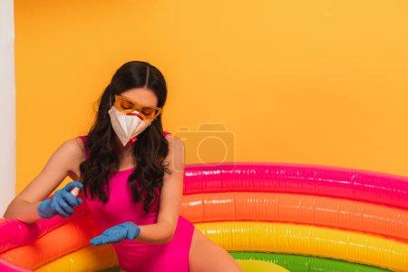 Photo pour Jeune femme en maillot de bain, lunettes de soleil, gants en latex et masque médical assis dans la piscine gonflable et appliquant un désinfectant sur jaune - image libre de droit