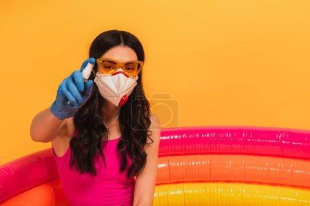 Photo pour Jeune femme en maillot de bain, lunettes de soleil et masque médical assis dans la piscine gonflable et tenant désinfectant sur jaune - image libre de droit