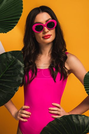 Photo pour Fille élégante en lunettes de soleil et maillot de bain debout avec les mains sur les hanches près de feuilles de palmier vert sur jaune - image libre de droit