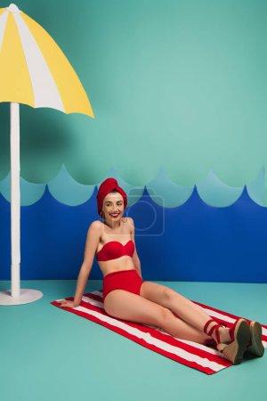Photo pour Femme gaie en serviette rouge et maillot de bain assis près des vagues coupées en papier bleu - image libre de droit