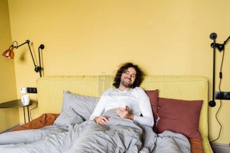 Photo pour Heureux jeune homme souriant tout en bavardant sur smartphone au lit - image libre de droit