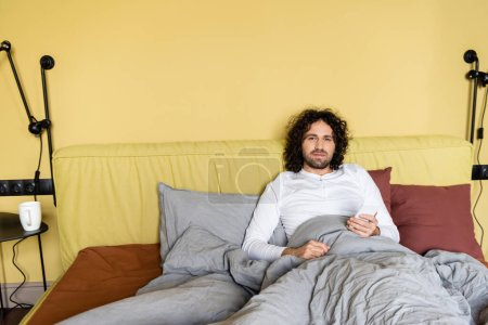 serious, curly man looking at camera while chatting on smartphone in bed