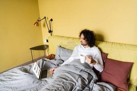 Photo pour KYIV, UKRAINE - 25 AVRIL 2020 : vue grand angle de pigiste à l'aide d'un ordinateur portable avec site Youtube tout en tenant une tasse de café au lit - image libre de droit