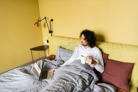 Photo for High angle view of young freelancer using laptop with tickets online website while holding cup of coffee in bed - Royalty Free Image