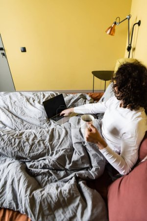 Photo for High angle view of curly freelancer using laptop with blank screen while holding cup of coffee in bed - Royalty Free Image