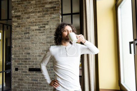 handsome man in pajamas drinking coffee while standing with hand on hip and looking at camera
