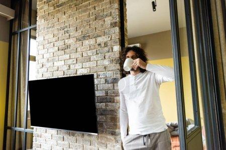 Photo pour Jeune homme en pyjama boire du café tout en se tenant près de l'écran LCD vierge accroché au mur de briques - image libre de droit
