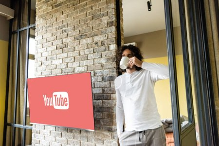 Photo pour KIEV, UKRAINE - 25 AVRIL 2020 : young man in pajamas drinking coffee while standing near lcd screen with Youtube website - image libre de droit