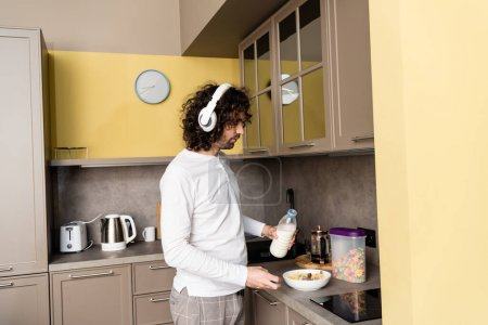 Photo for Young man in pajamas and wireless headphones pouring milk into bowl with flakes while preparing breakfast - Royalty Free Image