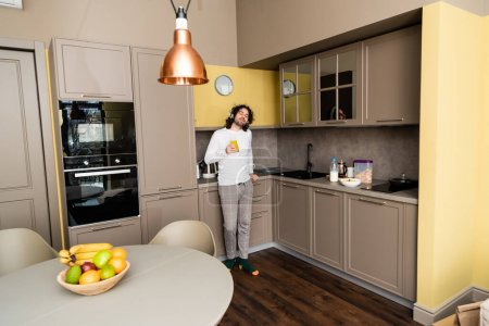 dreamy young man listening music in wireless headphones with closed eyes while holding orange juice in kitchen