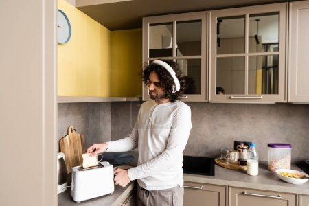 Photo for Curly man in wireless headphones putting bread into toaster while preparing breakfast - Royalty Free Image