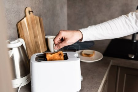Photo for Partial view of man taking bread out of toaster in kitchen - Royalty Free Image
