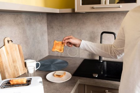 cropped view of man holding tasty fried bread near toaster in kitchen