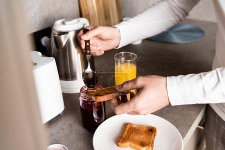 Photo pour Vue partielle de l'homme écartant la confiture sur le pain grillé pour le petit déjeuner - image libre de droit