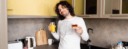 horizontales Bild eines fröhlichen Mannes mit Orangensaft und Toast mit Marmelade, während er in die Kamera lächelt