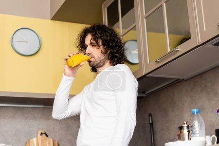 Foto de Vista de ángulo bajo del hombre reflexivo beber jugo de naranja mientras está de pie en la cocina - Imagen libre de derechos