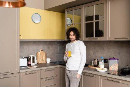 Photo pour Homme triste dans les pyjamas regarder la caméra en tenant un verre de jus d'orange dans la cuisine - image libre de droit