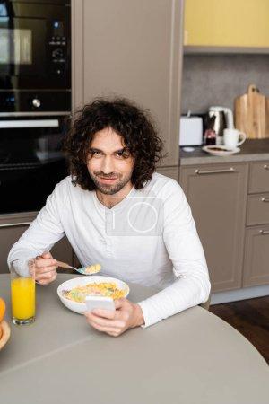 Photo pour Homme heureux souriant à la caméra tout en prenant le petit déjeuner et bavarder sur smartphone dans la cuisine - image libre de droit
