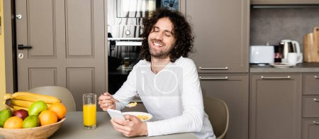 Photo for Panoramic shot of smiling man chatting on smartphone during breakfast in kitchen - Royalty Free Image