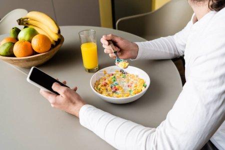 Photo pour Vue recadrée de l'homme tenant smartphone avec écran blanc tout en prenant le petit déjeuner - image libre de droit