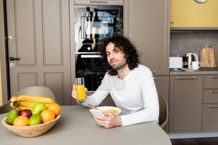 schöner Mann blickt in die Kamera, während er Orangensaft in der Hand hält und während des Frühstücks das Smartphone benutzt