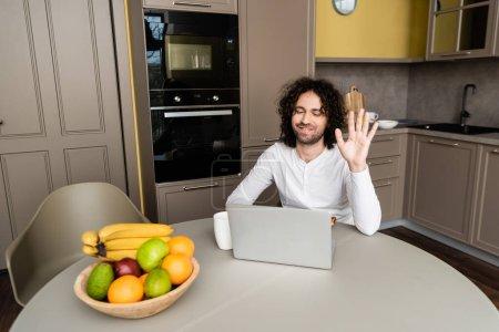 Photo pour Heureux freelancer agitant la main pendant le chat vidéo sur ordinateur portable près tasse de café et fruits frais - image libre de droit