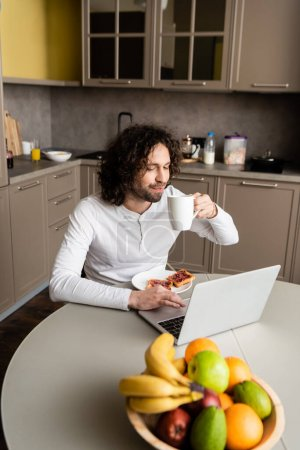 Photo for Selective focus of freelancer drinking coffee near laptop, toasts and fresh fruits - Royalty Free Image