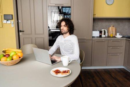 Photo pour Vue arrière de pigiste à l'aide d'un ordinateur portable avec site web shopping à l'écran près de tasse de café, des toasts et des fruits frais - image libre de droit